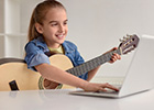 Image of young girl learning to play a guitar